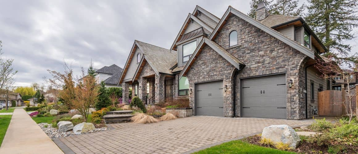 Large stone house with stone driveway.